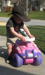 Boy climbing onto a pink toy car.